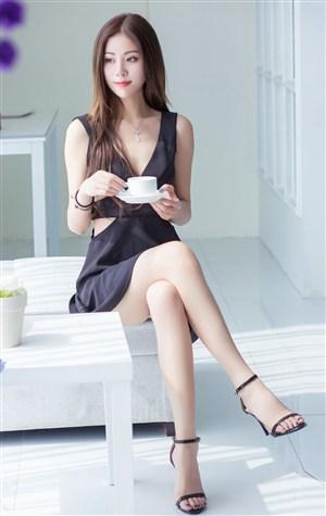 端咖啡杯的长腿美女