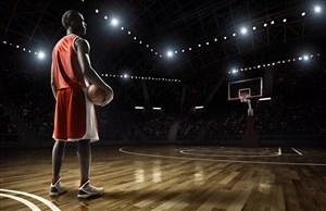 站在黑暗的籃球場上的籃球隊員