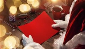 正在用紅紙做禮盒的圣誕老人高清攝影圖片