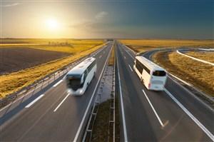 两条路上行驶的白色大巴车