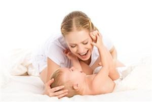 抱著嬰兒大笑的媽媽高清攝影圖