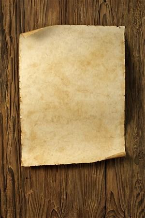 木桌上的泛黃的紙張高清攝影圖
